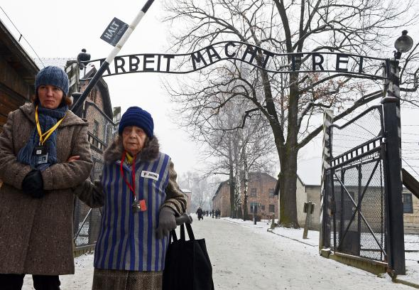 A former concentration camp prisoner, right, attends a ceremony at the memorial site of the former Nazi concentration camp Auschwitz-Birkenau in Oswiecim, Poland, on Jan. 27, 2014. Photo by Janek Skarzynski/AFP/Getty Images