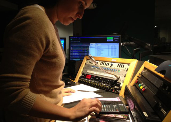 All Things Considered director Monika Evstatieva during a live broadcast in NPR's Studio 2A, where clocks abound.