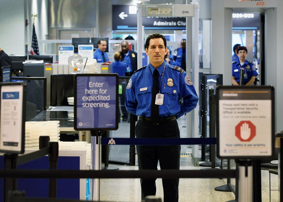 127987024-agent-waits-for-passengers-to-use-the-tsa-precheck-lane