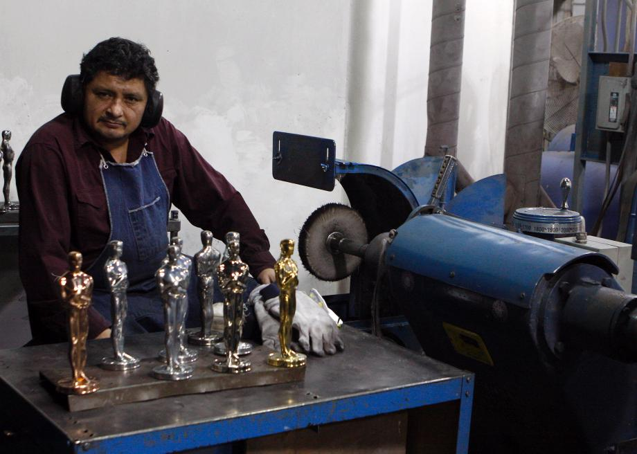96836383-alvaro-landa-rests-while-polishing-oscar-statues-at-the