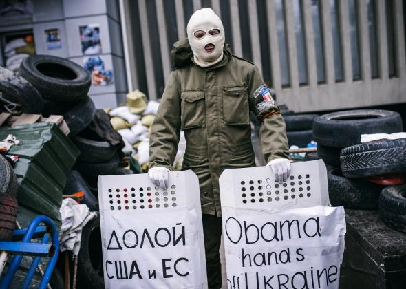 484357413-masked-pro-russia-supporter-stands-guard-outside-the