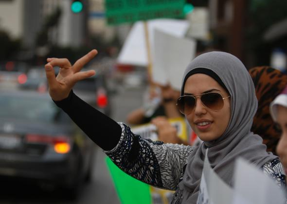 152593473-woman-makes-a-peace-sign-gesture-as-muslim-congress