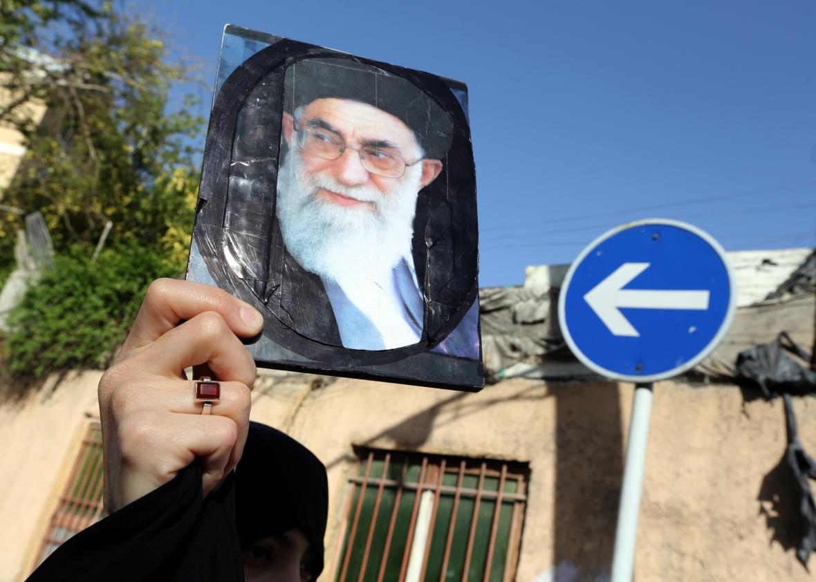 469589878-an-iranian-woman-holds-a-portrait-of-irans-supreme