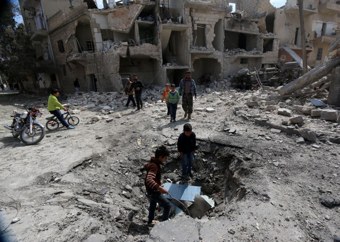 470327304-syrians-inspect-a-crater-on-the-ground-left-by-a