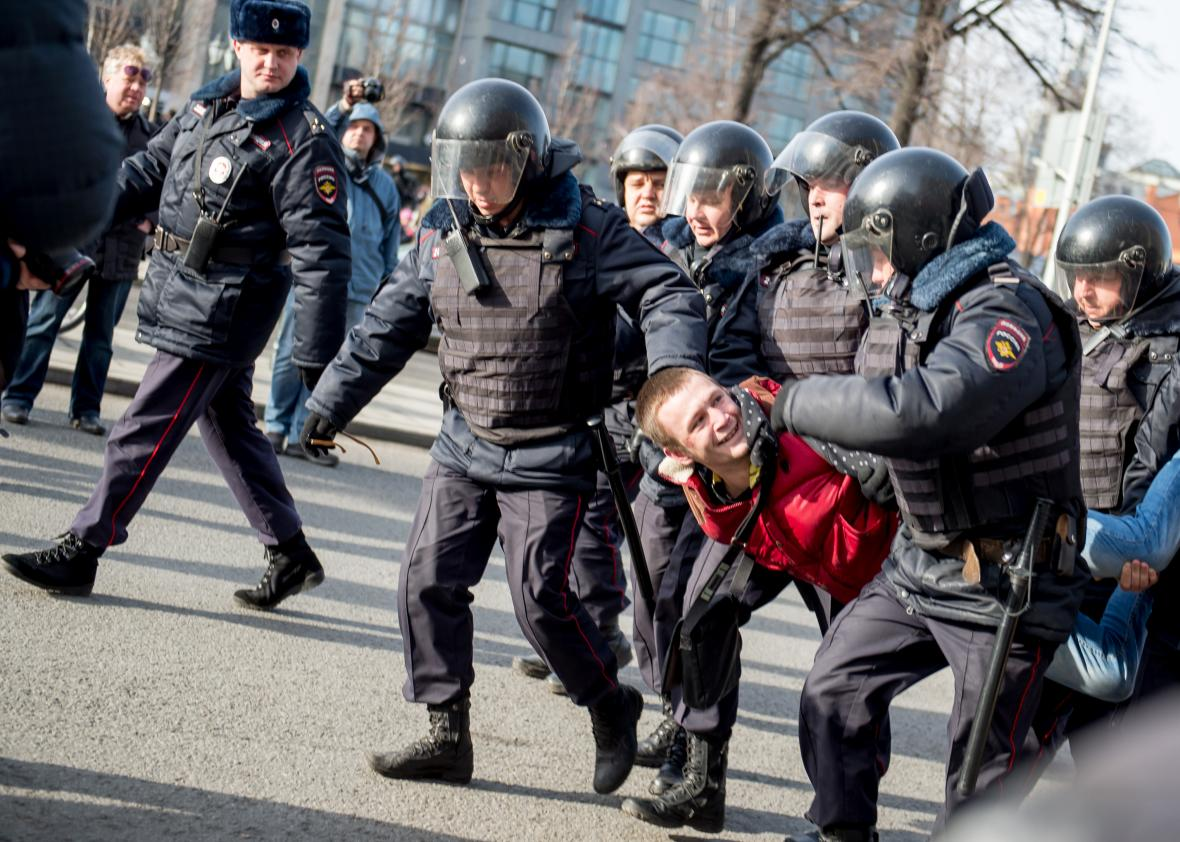 657967098-riot-police-officers-detain-a-man-during-an