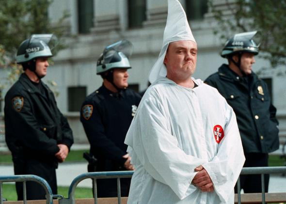 152898655-ku-klux-klan-member-stands-with-heavy-police-protection