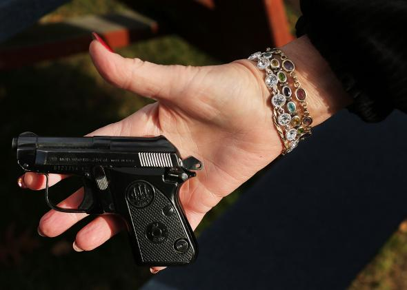 158638982-woman-holds-a-beretta-pistol-at-a-gun-buyback-event-at