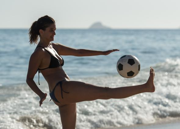 468056931-woman-plays-with-a-football-at-ipanema-beach-in-rio-de