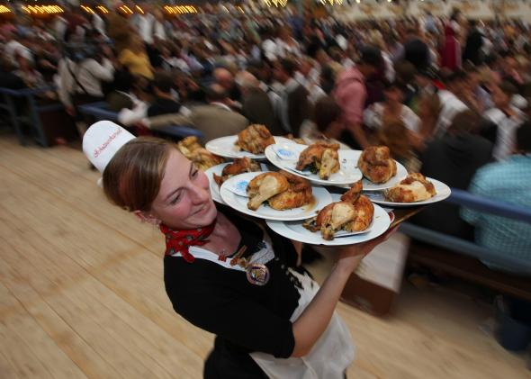 152565499-waitress-carries-grilled-chicken-at-a-beer-tent-during