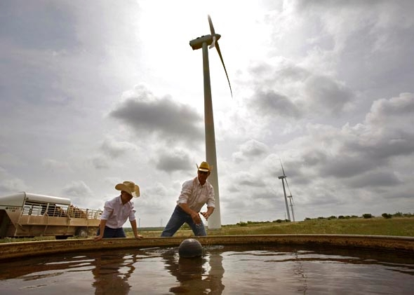 Clifton Brandon, 43, and his son, Teagan, 10 years, clean a water tank for their 300-head of black angus cattle on the Lone Star Wind Farm 17 miles north of Abilene, Texas June 9, 2007.
