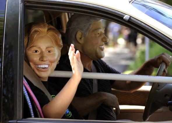 103179810-tourists-in-bill-and-hillary-clinton-masks-drive