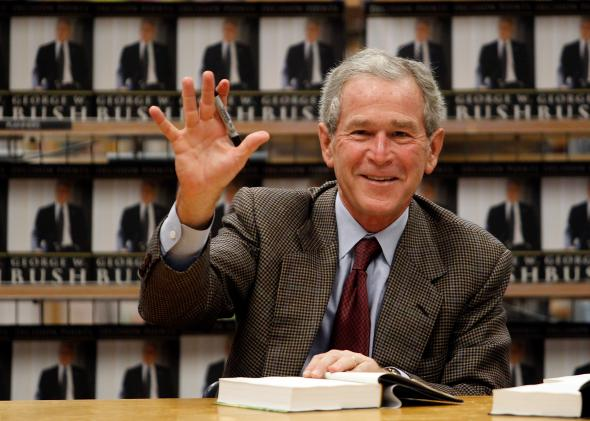 106650115-former-u-s-president-george-w-bush-waves-while-signing