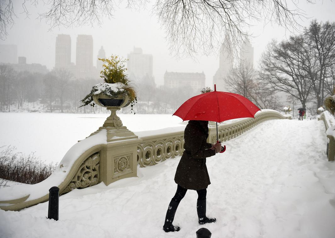 506425930-woman-walks-in-strong-winds-and-heavy-snow-fall-in